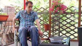 Junger Mann im Rollstuhl, der traurig sich fühlt stock video footage