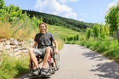 Junger Mann im Rollstuhl draußen Lizenzfreie Stockbilder