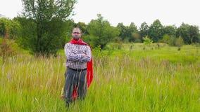 Junger Mann im roten Umhang, der herum, die Weise und den Lauf wählend schaut stock footage
