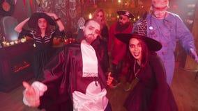 Junger Mann im schlechten Vampirskostümtanzen mitten in einer Gruppe Freunden, die Halloween feiern stock video footage