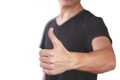 Junger Mann im schwarzen T-Shirt zeigt sich Daumen Lokalisiert auf weißem BAC Lizenzfreie Stockfotos