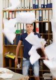 Junger Mann im sehr unordentlichen Büro mit dem Dokumentenfliegen Stockbild