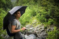 Junger Mann im Stoff, grüne Berge, die einen Regenschirm halten Stockbild