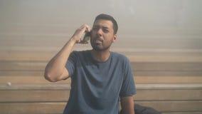 Junger Mann im T-Shirt, das emotionales Telefongespräch draußen hat stock footage