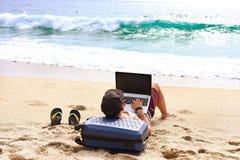 Junger Mann im Trägershirt, in den kurzen Hosen, in der Hysteresenkappe am Strand mit Laptop u. im Koffer Freiberufler, Hippie Bl Lizenzfreie Stockfotos