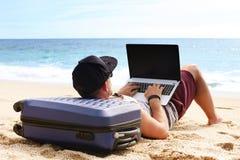 Junger Mann im Trägershirt, in den kurzen Hosen, in der Hysteresenkappe am Strand mit Laptop u. im Koffer Freiberufler, Hippie Bl Stockbilder