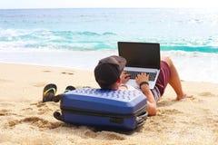 Junger Mann im Trägershirt, in den kurzen Hosen, in der Hysteresenkappe am Strand mit Laptop u. im Koffer Freiberufler, Hippie Bl Stockfotografie