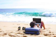 Junger Mann im Trägershirt, in den kurzen Hosen, in der Hysteresenkappe am Strand mit Laptop u. im Koffer Freiberufler, Hippie Bl Lizenzfreies Stockfoto