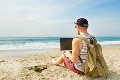 Junger Mann im Trägershirt, in den kurzen Hosen, in der Hysteresenkappe am Strand mit Laptop u. im Rucksack Freiberufler, Hippie  Stockbild