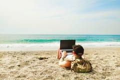 Junger Mann im Trägershirt, in den kurzen Hosen, in der Hysteresenkappe am Strand mit Laptop u. im Rucksack Freiberufler, Hippie  Lizenzfreies Stockbild