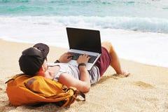 Junger Mann im Trägershirt, in den kurzen Hosen, in der Hysteresenkappe am Strand mit Laptop u. im Rucksack Freiberufler, Hippie  Lizenzfreie Stockbilder