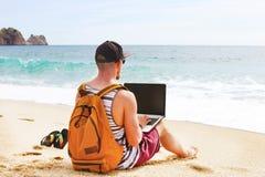 Junger Mann im Trägershirt, in den kurzen Hosen, in der Hysteresenkappe am Strand mit Laptop u. im Rucksack Freiberufler, Hippie  Stockfotos