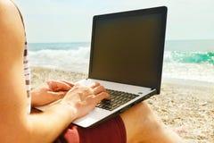 Junger Mann im Trägershirt, kurze Hosen, Hysteresenkappenkodierung auf Laptop am Strand Freiberufler, Hippie Blogger, Werbetexter Stockfotos