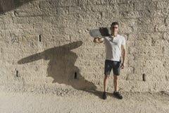 Junger Mann im Tunnel mit der Skateboardaufstellung stockbilder