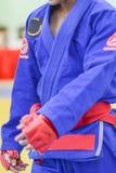 Junger Mann im weißen Kimono für Sambo, Judo, Jiu-Jitsu, das auf dem weißen Hintergrund, gerade schauend, Position des kämpfenden stockfoto