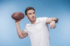 Junger Mann im weißen T-Shirt, das Fußball mit Rugbyball spielt Stockbilder