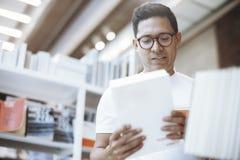Junger Mann im weißen T-Shirt Lesebuch mit Blinddeckel in einem Buchladen Stockfoto