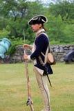 Junger Mann im Zeitraumkleid, Gebrauch der Muskete zeigend, Fort Ticonderoga, New York, 2014 Lizenzfreie Stockfotos