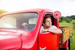 Junger Mann innerhalb des roten Weinlesekleintransporters, grüne Natur Stockfoto