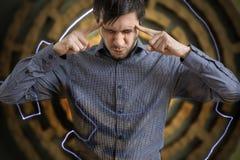 Junger Mann ist konzentriert suchend und nach Lösung für schwierige Aufgabe Stockbild