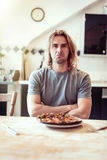 Junger Mann ist mit seiner gebrannten Pizza für das Mittagessen unglücklich Lizenzfreies Stockfoto