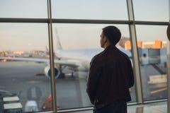 Junger Mann ist stehendes nahes Fenster am Flughafen und am aufpassenden Flugzeug vor Abfahrt Fokus auf seinem zurück Lizenzfreie Stockfotos