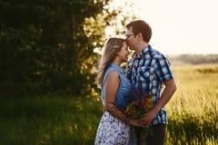 Junger Mann küsst das Mädchen auf der Stirn bei Sonnenuntergang lizenzfreie stockbilder