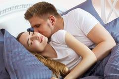 Junger Mann küsst seine Freundin im Bett morgens im Schlafzimmer, junges glückliches Paar, Familienwerte stockbilder