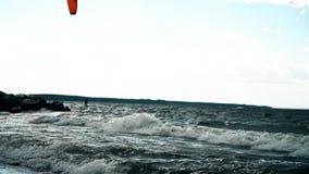 Junger Mann Kitesurfing im Ozean Starke Wellen, die über Steinen spritzen stock video footage