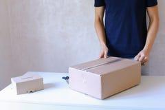 Junger Mann-Kleber-Band-Kasten und nimmt Paket in die Hand und steht in P Lizenzfreie Stockbilder