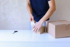 Junger Mann-Kleber-Band-Kasten und nimmt Paket in die Hand und steht in P Stockbild