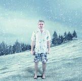 Junger Mann kleidete in der Sommerkleidung im Schnee an Stockfotos