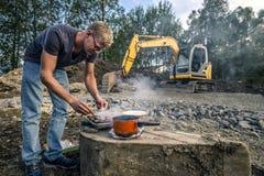 Junger Mann kocht Würste in der Front des Baus Lizenzfreie Stockfotos