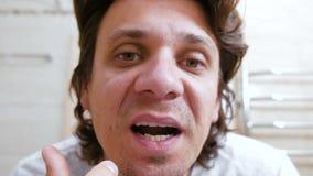 Junger Mann kommt ins Badezimmer Spiegel und drückt heraus einen Pickel unter seiner Nase zusammen Rosafarbene Lippen stock video