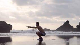 Junger Mann kurz gesagt und Turnschuhe, die Übungen auf einem Strand mit Felsen morgens oder der Glättung früh ausdehnend tun stock video footage