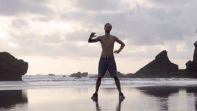 Junger Mann kurz gesagt und Turnschuhe, die ?bungen auf einem Strand mit Felsen morgens oder der Gl?ttung fr?h ausdehnend tun stock footage