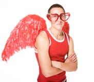 Junger Mann lächelt in den roten Innergläsern mit Flügeln O lizenzfreies stockfoto