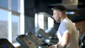 Junger Mann läuft auf Tretmühle im Sportverein stock video