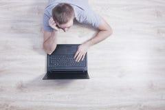 Junger Mann liegt auf dem Boden mit einem Laptop stockfotos