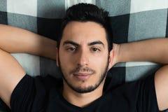 Junger Mann liegt im Bett lizenzfreies stockfoto