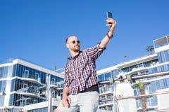 Junger Mann machen selfie nahe dem Strandhotel Stockbilder