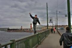 Junger Mann macht lebensbedrohenden Weg auf Geländer der Brücke Lizenzfreies Stockbild