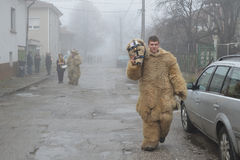 Junger Mann maskiert als Bär in einer nebeligen Dorfstraße Lizenzfreies Stockfoto