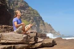 Junger Mann meditiert auf Felsen Stockfoto