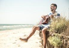 Junger Mann mit Akustikgitarre auf dem Strand, das Konzept der Freizeit und Kreativität Lizenzfreie Stockfotografie