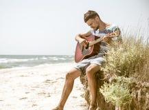 Junger Mann mit Akustikgitarre auf dem Strand, das Konzept der Freizeit und Kreativität Stockfotografie