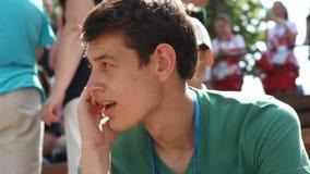 Junger Mann mit Ausweis spricht am Handy unter Zuschauern stock footage