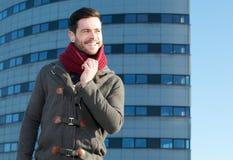 Junger Mann mit Bart draußen lächelnd mit Jacke und Schal Lizenzfreie Stockbilder