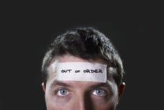 Junger Mann mit blauen Augen und Band simsen außer Betrieb auf Stirn im trockenen leeren Verstand Stockfotografie