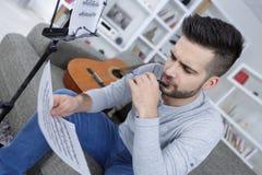 Junger Mann mit Buch für verfassende Musik mit Gitarre Stockbilder